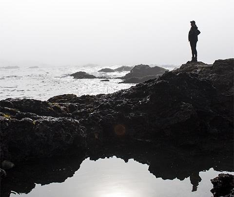 girl standing on rocks by ocean