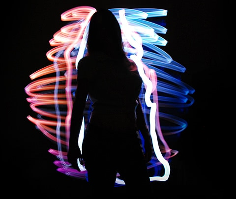 girl infront of light art